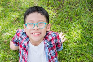 Young asian boy smiling on grass field